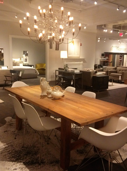 The Eva Zeisel wares sit on top of this sleek dining table, surrounded handsomely by modern white chairs.