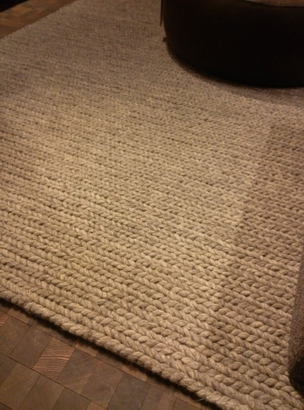 The knitted quality of this rug is so handsome, especially its gray tones against the dark wood floor.