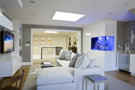 Lighting by Boyd; custom cabinetry by ADG Millwork; aquarium by ReefeScape; media wall by Absolute Custom Solutions; accent table by Edward Ferrell + Lewis Mittman