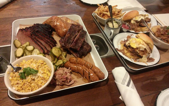This spread includes brisket, ribs, pork sausage with habanero and queso blanco, and a brisket sandwich with a fried egg on top.