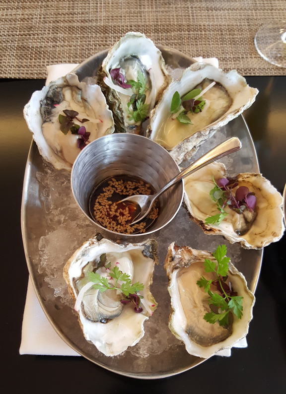 A platter of oysters with tender spring greens