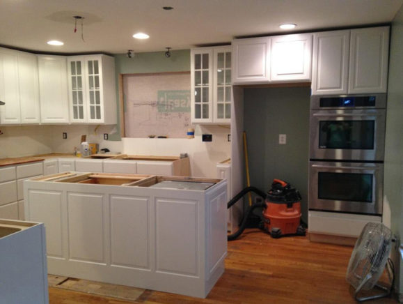 DURING RENOVATION: The removal of the sliding glass doors allowed us to add much needed cabinets for storage and a double oven, which the homeowner desperately wanted. We also removed the bulkhead to make space for taller cabinets. A larger window was installed above the sink to bring in more natural light.