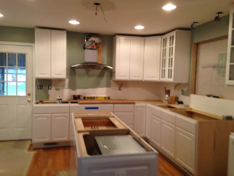 DURING RENOVATION: We relocated the refrigerator to the adjacent wall, added cabinets and repositioned the stovetop to the back wall from the island, where it was originally located.