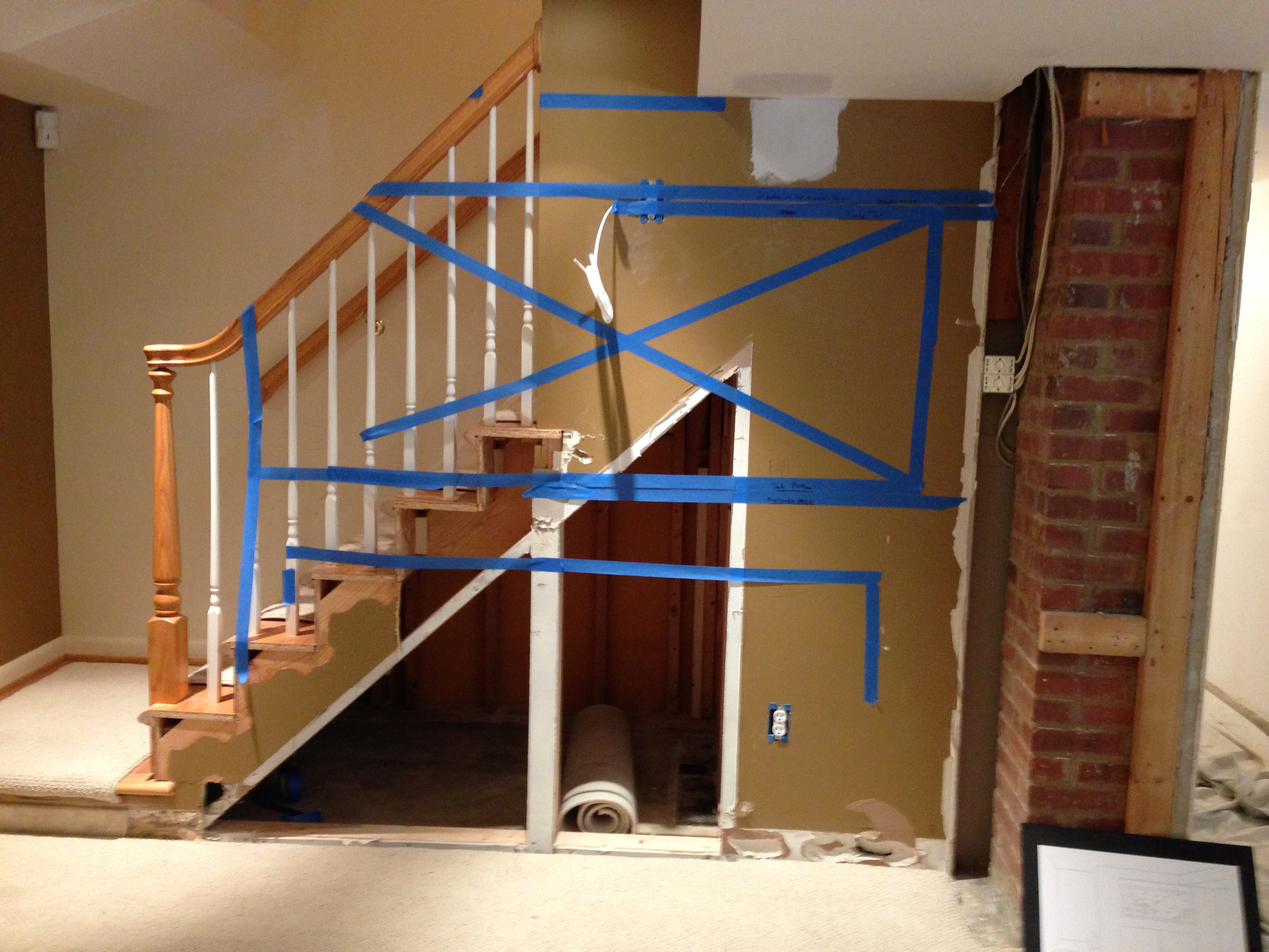 Staircase and lower well wall marked with blue tape to show aquarium position
