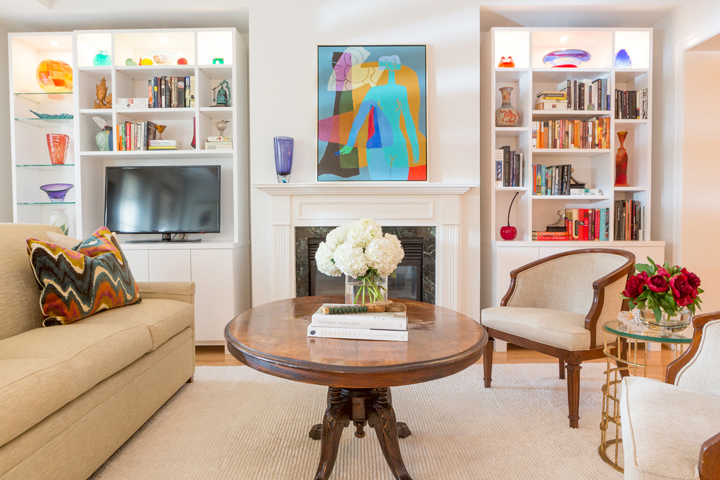 Chic living room with built-in shelving and colored-glass accessories by Shawna Underwood Interior Design