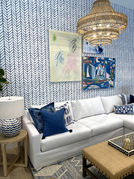 living room with modern blue chevron wallpaper, rattan chandelier and rattan ottoman at Serena & Lily in Bethesda, Maryland. Painting by Sarah Trundle and Lanie Mann
