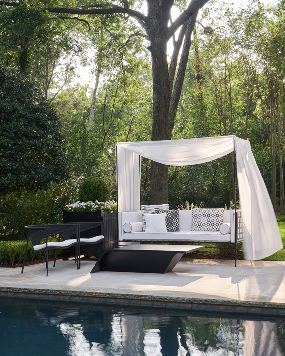 landscape and pool deck, fire pit with chaise longues and a swing by Dedon at the 2020 Kips Bay Dallas Showhouse