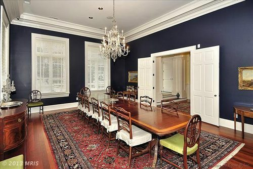 Oh, goodie! Another chandelier and big imposing Oriental rug—paired weirdly with casual slipcovered chairs. I don't get the dark blue paint, either.