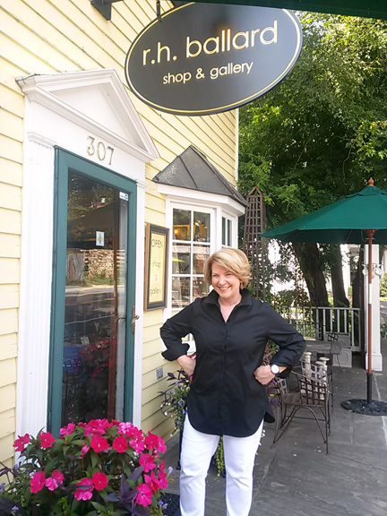 Joannie Ballard poses in front of her shop on Main Street.