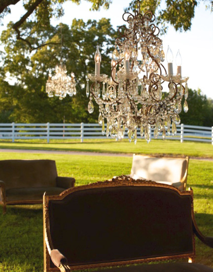 For this wedding, she hung chandeliers in the trees and lit them using extension cords. The lighting and settees all came from her warehouse.