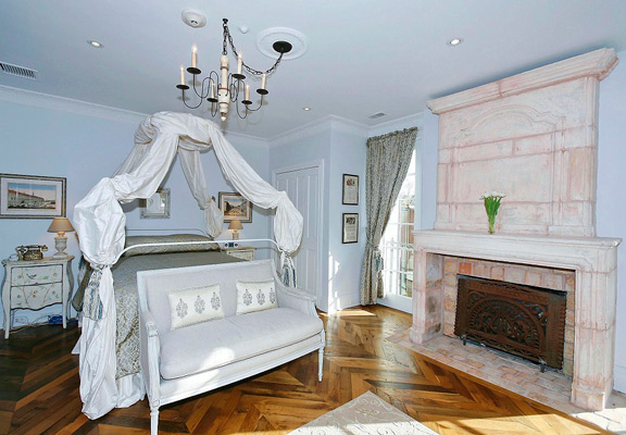 The aforementioned chevron flooring and one of the fireplaces—I adore that sweet settee at the end of the bed.