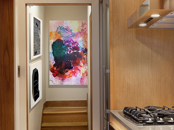 """Abstract painting on rear wall: """"Boom,"""" a tissue-ink monoprint by Maya Freelon Asante. Art provided by Morton Fine Arts Gallery. Side wall: top painting: """"I Can See Your House From Here,"""" pastel on paper by Osi Audu; on bottom: Self Portrait XXXIV, graphite on paper by Osi Audu."""