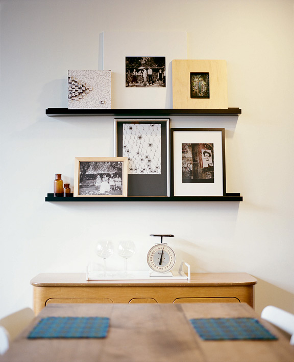 The floating shelves above the sideboard next to their dining table are home to an ever-changing gallery of art.
