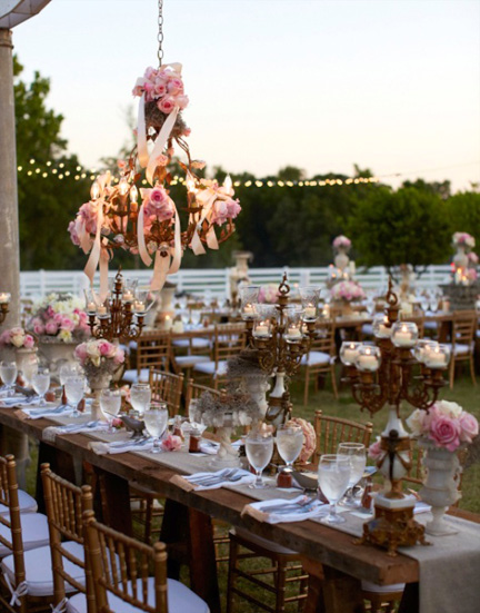 Braher keeps a warehouse of furnishings and accessories for events and photo shoots. This was a wedding on a MIssissippi farm, using  planks on saw horses and dressed with runners made from fabric remnants at Jo-Ann Fabric and Craft Stores.
